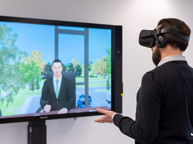 Jan Fiedler trägt eine Virtual Reality Brille, steht vor einem Monitor, auf dem KI-gestützte Avatare zu sehen sind